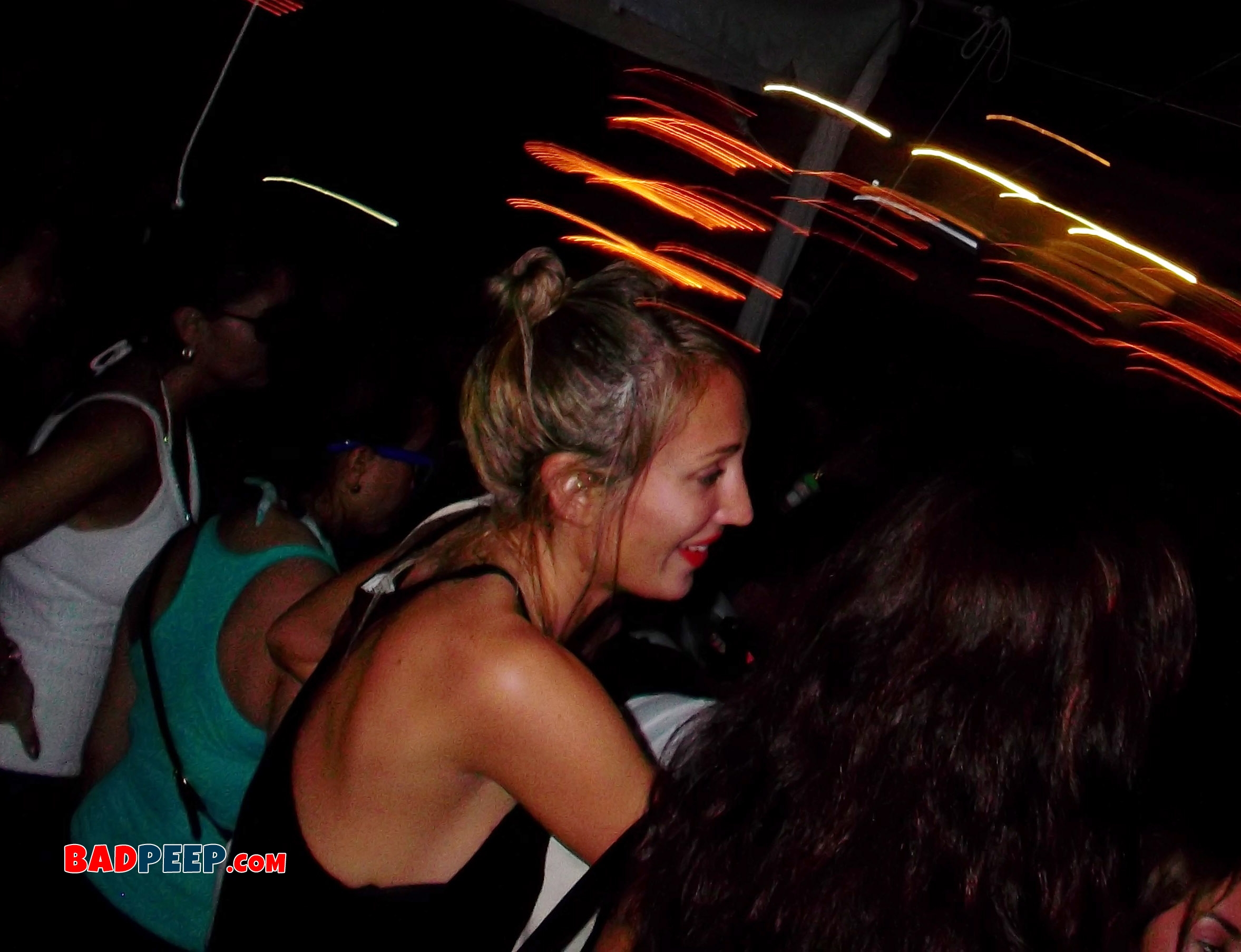 Smiling girl in crowded nightclub